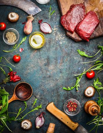 Verse biefstuk, houten lepel, mes en aromatische kruiden, specerijen en groenten voor het koken, op rustieke achtergrond, bovenaanzicht, frame.
