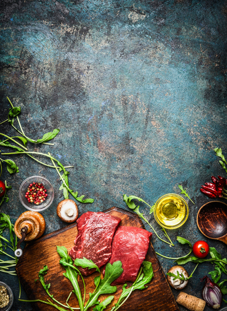 dark meat: Beef steak and various ingredients for cooking on rustic wooden background, top view, frame.  Healthy, diet food concept. Stock Photo