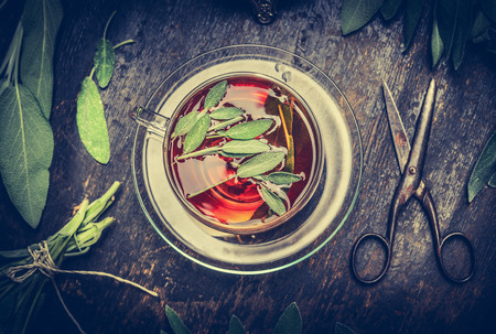 retro dark: Herbal tea, old scissors and sage leaves on dark rustic wooden background, top view. Retro toned