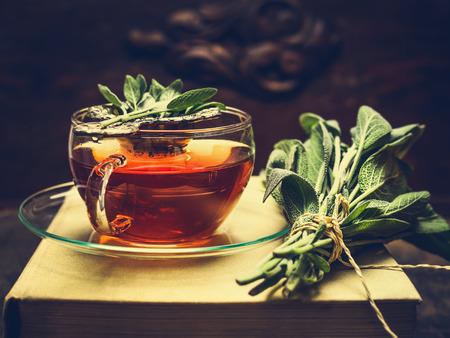 taza de té: té de hierbas hecho a partir de salvia en vaso de vidrio que se coloca en los libros, en las inmediaciones se encuentra un manojo de salvia sobre fondo oscuro de madera. Retro tonos. Foto de archivo