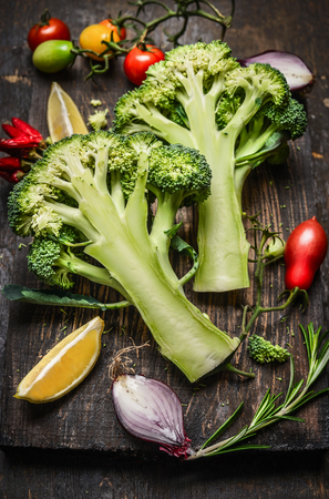 cruciferous: fresh broccoli, cut into halves with ingredients for cooking, close up.  Vegan food , vegetarian and  healthily cooking concept.