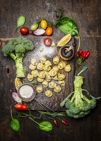healthily: Tortellini with fresh vegetables, preparation with flour on rustic wooden background, top view. Vegetarian food and healthily cooking concept.