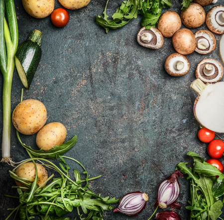 Fresh organic seasonal garden vegetables for cooking on rustic wooden background, top view, frame, place for text.  Vegan food , vegetarian , diet or healthily cooking concept.