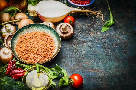 Lentil with fresh vegetables and ingredients for cooking on blue rustic background, close up. Vegan food, vegetarian, diet or healthily cooking concept.
