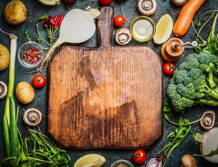 концепция: Свежие овощи и ингредиенты для приготовления пищи вокруг старинных разделочной доске на деревенском фоне, вид сверху, место для текста. Веганский питание, вегетарианское и здоровой пищи концепцию.