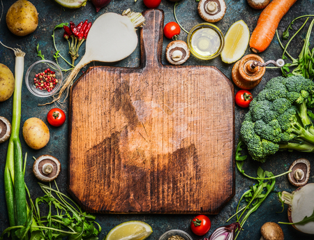 ingredient: Fresh vegetables and  ingredients for cooking around vintage cutting board on rustic background, top view, place for text.  Vegan food , vegetarian and healthily cooking concept. Stock Photo