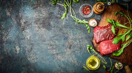 �cooking: Filete de carne de vaca cruda y los ingredientes frescos para cocinar en el fondo r�stico, vista desde arriba, bandera. Concepto de alimentos saludables y la dieta.