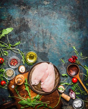 brasiere: Pechuga de pollo, cuchara de madera y deliciosos ingredientes frescos para cocinar en el fondo r�stico, vista desde arriba, marco. Saludable, dieta o Deportes concepto de nutrici�n.