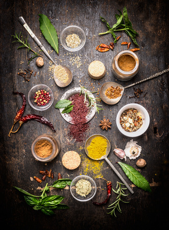 flavoring: composition of hot spices and fresh flavoring herbs on dark rustic wooden background, top view Stock Photo