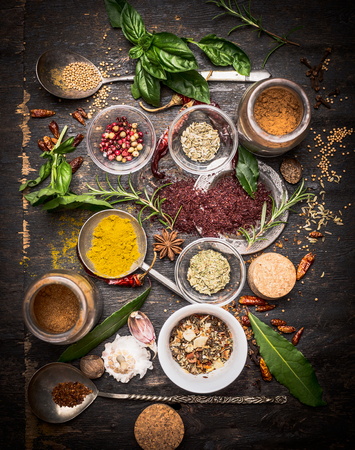 acetic: variety of oriental herbs and spices: Acetic tree, curry powder, paprika, cayan pepper, sira,Bay leaf on spoons and bowls, top view.  national cuisine  and cooking concept. Stock Photo