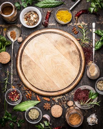 様々 なハーブやスパイスの素朴な木製の背景、トップ ビューで空のカッティング ボードの周り。創造的な料理と料理の概念。