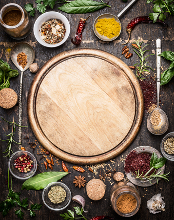 overhead view: variety of herbs and spices  around empty cutting board on rustic wooden background, top view.Creative and national cuisine  and cooking concept. Stock Photo