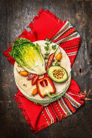 taco: Tortillas and vegetables ingredients for burrito or tacos on dark wooden background, top view