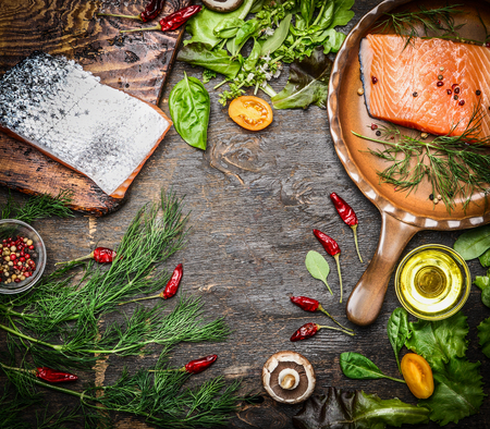 pans: Fresh salmon fillet with ingredients for tasty cooking on rustic wooden background, top view, frame. Healthy food concept. Stock Photo