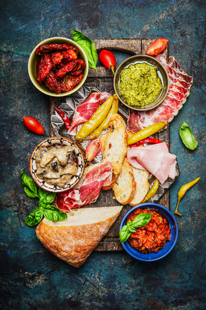Delicious antipasti ingredients  for  bruschetta or crostini making on rustic background, top view. Italian food concept