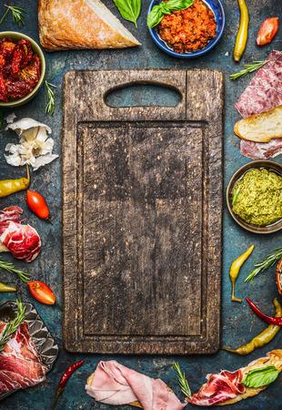 saucisse: Divers ingrédients pour bruschetta ou crostini décision: viande fumée, saucisses, jambon, pesto, tomates séchées, peperoni autour vierge ancien conseil de coupe sur fond rustique, vue de dessus. concept de la cuisine italienne.