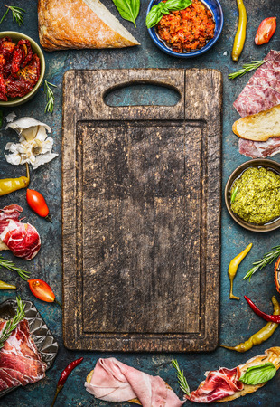Various ingredients for bruschetta or crostini making: smoked meat, Sausage, ham ,pesto, dry tomatoes, peperoni around blank old cutting board on rustic background, top view. Italian food  concept. Stock Photo