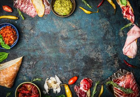 comida italiana: Ingredientes para aperitivo italiano, bruschetta, crostini o la barra de sándwich con jamón italiano, salchichas y antipasto en el fondo de madera rústica, vista desde arriba, marco