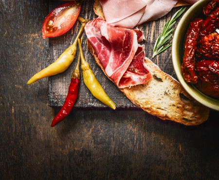 meat dish: bruschetta or crostini with italian ham and antipasto on dark wooden background, close up