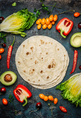 taco tortilla: Ingredients for tacos or burrito making.  Fresh organic vegetables and tortillas on rustic background, top view, place for text