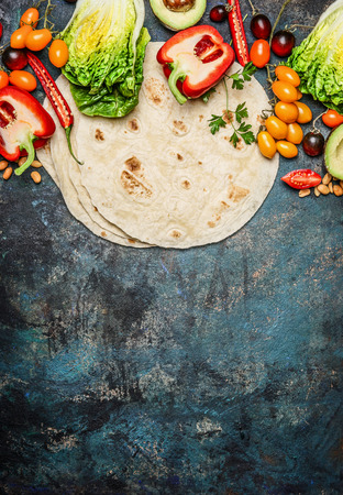 Ingredients for tacos : various fresh organic vegetables and tortillas on rustic background, top view, place for text