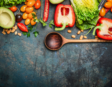 overhead: Colorful organic vegetables with wooden spoon , ingredients for salad or filling on rustic wooden background, top view. Healthy food or diet cooking concept.