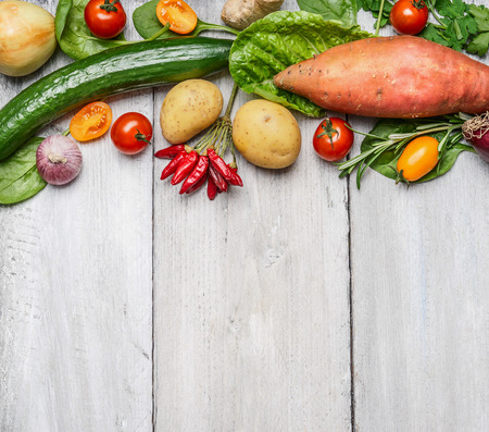 Fresh organic farm vegetables and ingredients for healthy cooking on white wooden background, border, top view. Vegetarian or diet food concept Stockfoto