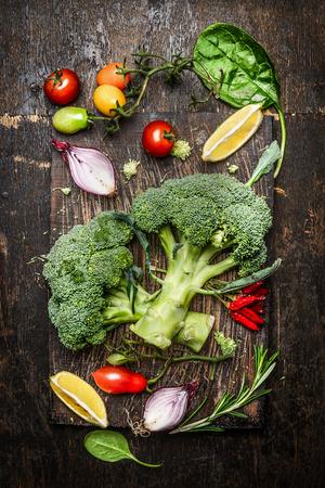 Frischer Brokkoli und Gemüse Zutaten und Gewürze für leckere vegetarische Küche auf rustikalem Holzuntergrund, Draufsicht. Diät oder vegane Ernährung Konzept.