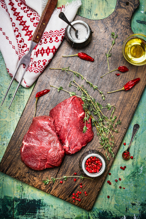 carne cruda: Raw meat steaks on wooden cutting board with oil, herbs and spices. Rustic background, top view