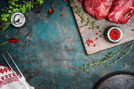 rare: Raw meat steaks with fresh seasonings on rustic wooden background, top view, frame
