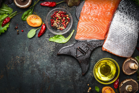 Salmon fillet with delicious ingredients for cooking on dark rustic wooden background, top view, frame. Healthy, diet or vegetarian food concept.