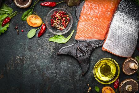 Zalmfilet met heerlijke ingrediënten voor het koken op een donkere rustieke houten achtergrond, bovenaanzicht, frame. Gezond, dieet of vegetarisch voedsel concept.