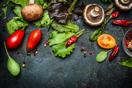 salads: Ingredients for tasty salad making: lettuce leaves,champignons, tomatoes, herbs and spices on dark rustic background, top view, border. Healthy, diet or vegetarian food concept.