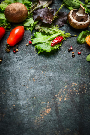 Fresh ingredients for tasty cooking and salad making on dark rustic background, top view, frame. Imagens