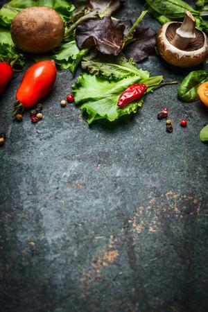 Verse ingrediënten voor smakelijke gerechten en salade maken op donkere rustieke achtergrond, bovenaanzicht, frame. Stockfoto