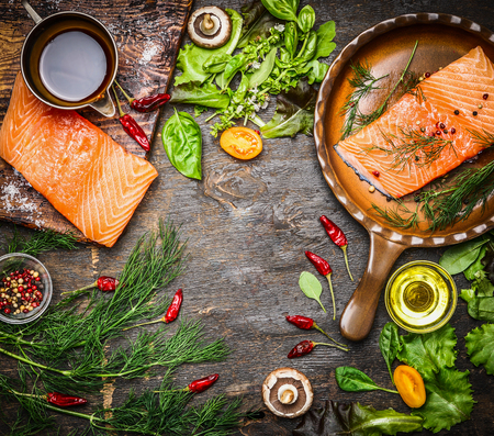 Salmon fillet on rustic kitchen table with fresh ingredients for tasty cooking and frying pan. Wooden background, frame, top view.  Healthy and diet food concept.