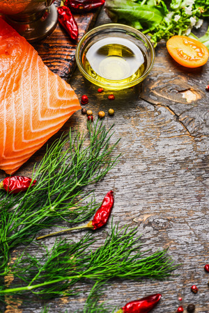 fish: Salmon fillet with oil and fresh hebrs and seasoning for cooking on rustic wooden background. Healthy and diet food concept.