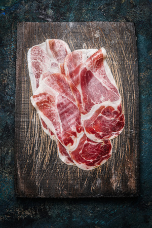 Regular Slices of Iberian hams on rustic wooden background, top view