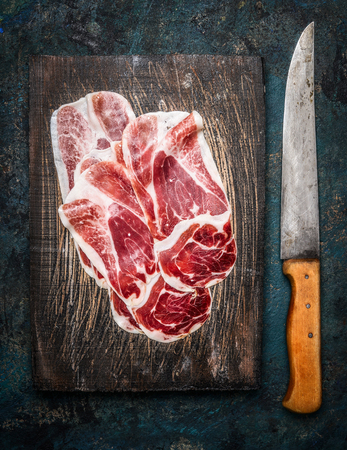 Slices of Iberico ham Cebo with kitchen knife on rustic wooden background, top view. Stock Photo