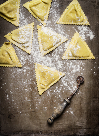 rustic food: ravioli  Triangoli making, preparation on rustic wooden background, top view. Italian food concept. Stock Photo