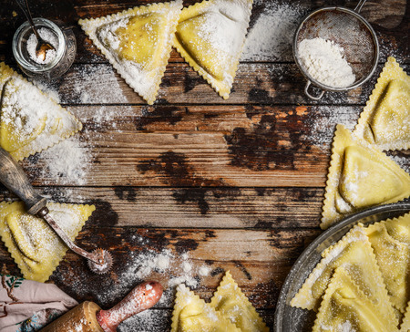 downloaded: Handmade ravioli Triangoli with kitchen tools on rustic wooden background, top view Stock Photo