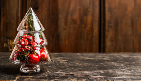 free christmas background: Christmas symbol  tree from glass with decoration on rustic table over wooden background, banner