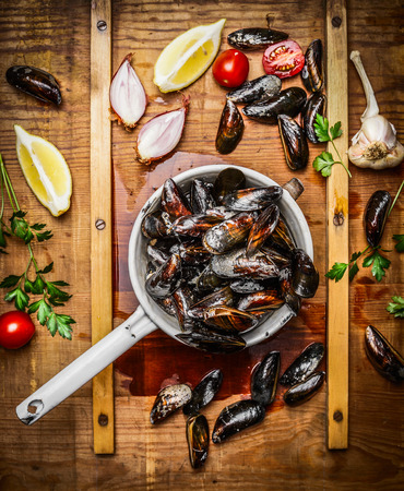 Fresh mussels in old colander with ingredients for tasty cooking on wooden background, top view. Seafood concept