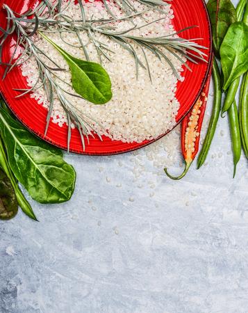 arroz blanco: Raw Rice, deliciosas verduras e ingredientes frescos para cocinar en el fondo de madera gris, vista desde arriba, en la frontera
