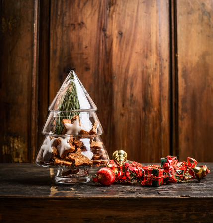 food concept: Glass christmas tree with cookies and decoration on rustic wooden background