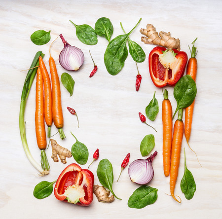 Fresh vegetables ingredients for cooking , composing on white wooden background, top view, frame. Healthy  food, vegetarian or diet nutrition concept.