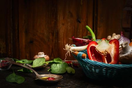 comidas: Verduras frescas en cesta azul, cuchara de cocina y los ingredientes en la mesa de la cocina rústica sobre fondo de madera. Concepto de alimentos saludables.