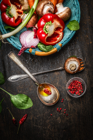 fresh vegetable: Fresh vegetables in basket, cooking spoons with oil and spices on rustic wooden background, top view. Vegetarian and Healthy food concept. Stock Photo