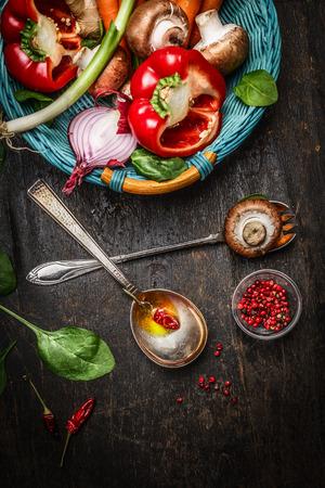 ensalada de verduras: verduras frescas en la cesta, cucharas de cocina con aceite y especias sobre fondo de madera r�stica, vista desde arriba. concepto de la comida vegetariana y saludable. Foto de archivo