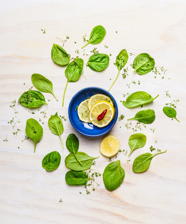 baby spinach: Fresh delicious baby spinach around bowl with lemon and spices on white wooden background, top view. Clean food concept.